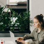 Une femme qui travaille sur un ordinateur devant un miroir avec des plantes