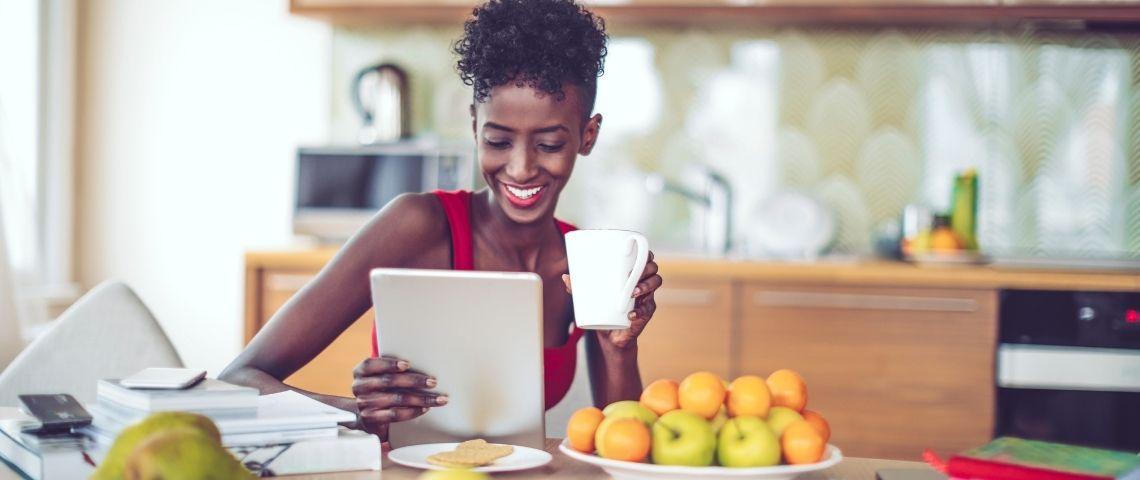 Une femme assise regarde sa tablette