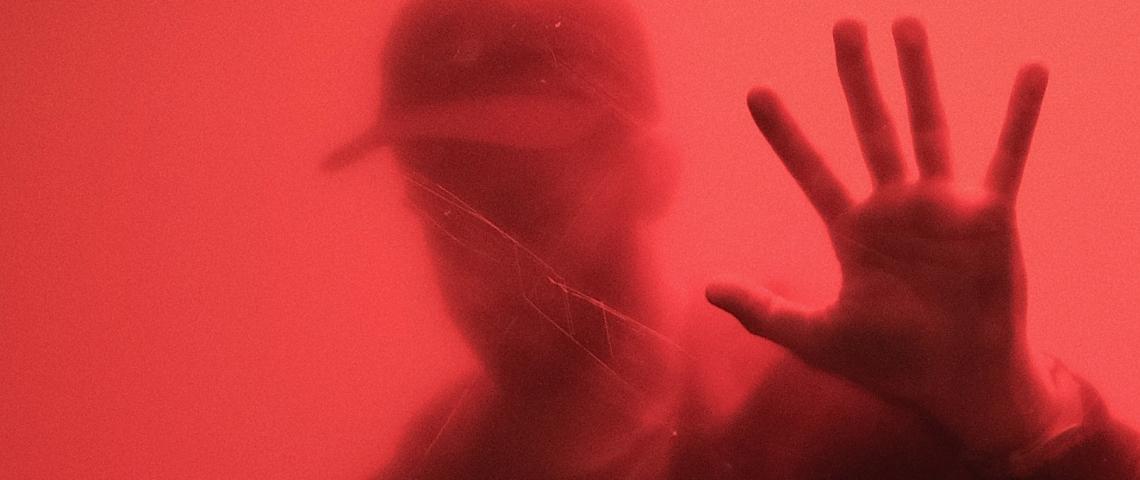 Un homme derrière une parois rouge.