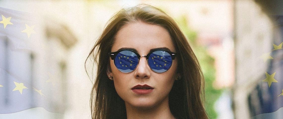 Jeune fille portant des lunettes de soleil dans lesquelles se reflète le drapeau européen