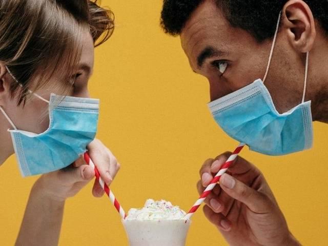 Un homme et une femme qui boivent un milkshake avec des masques chirurgicaux