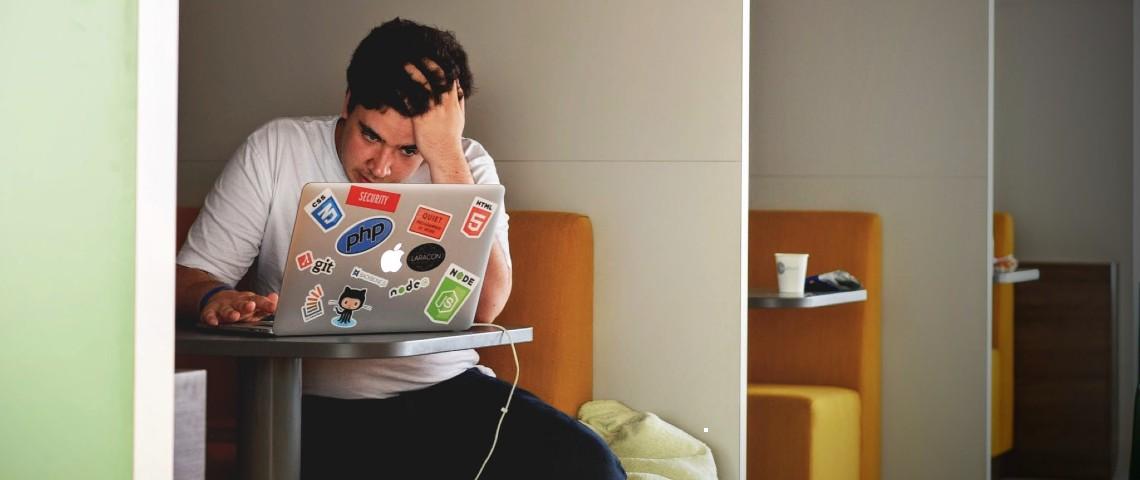 jeune homme devant un ordinateur l'air desespéré, seul dans une salle.
