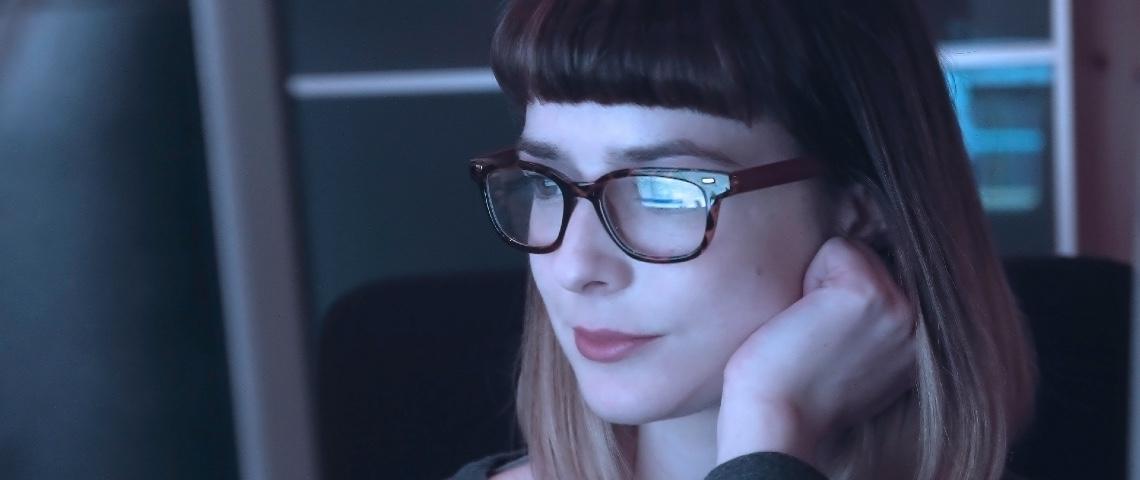 Femme portant des lunettes devant un ordinateur