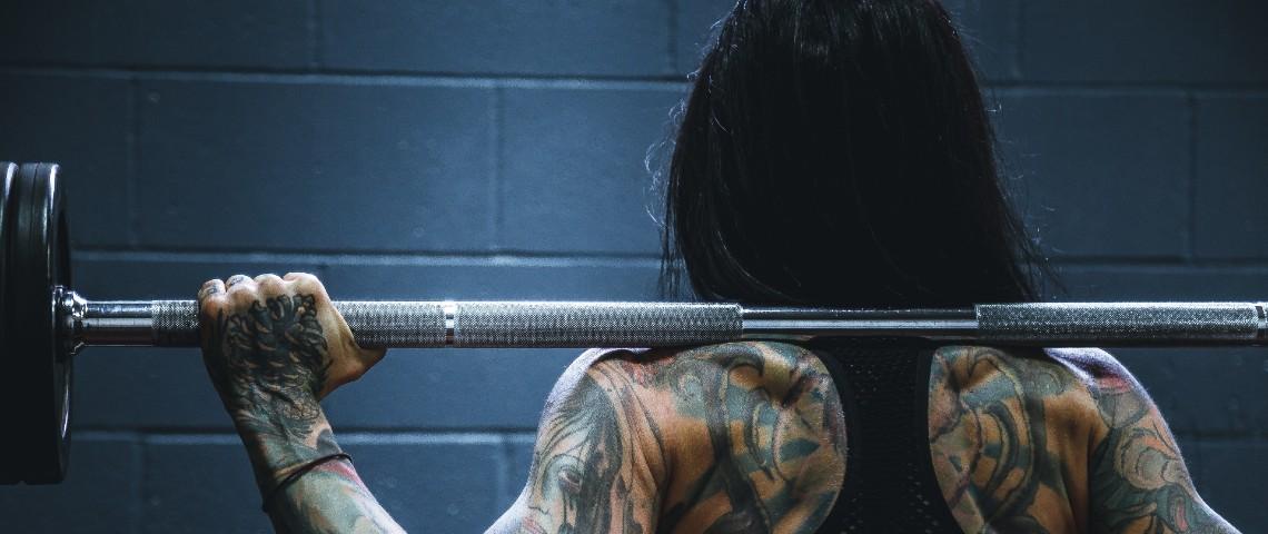 Une femme tatouée de dos porte un haltère