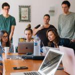 Un groupe d'adolescents en train de travailler en groupe autour d'ordinateurs