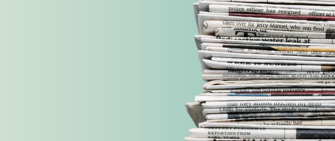 Tas de journaux sur fond vert.