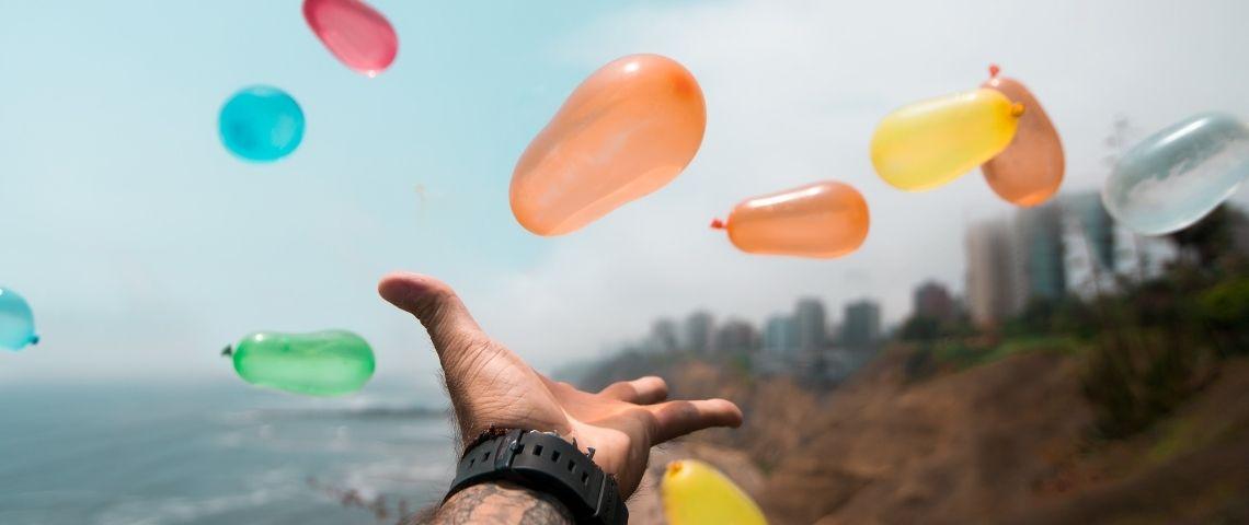 une main tendue vers des ballons