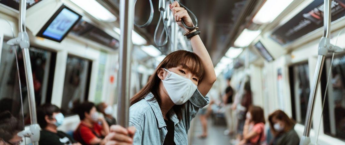 Une femme avec un masque dans le métro
