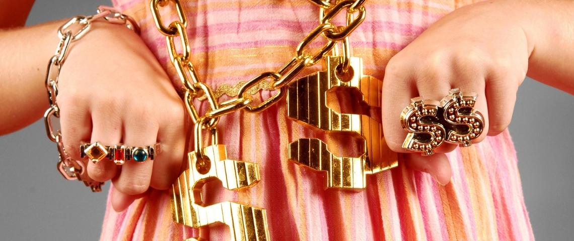 une fille avec des grosse bagues et des collier en or.