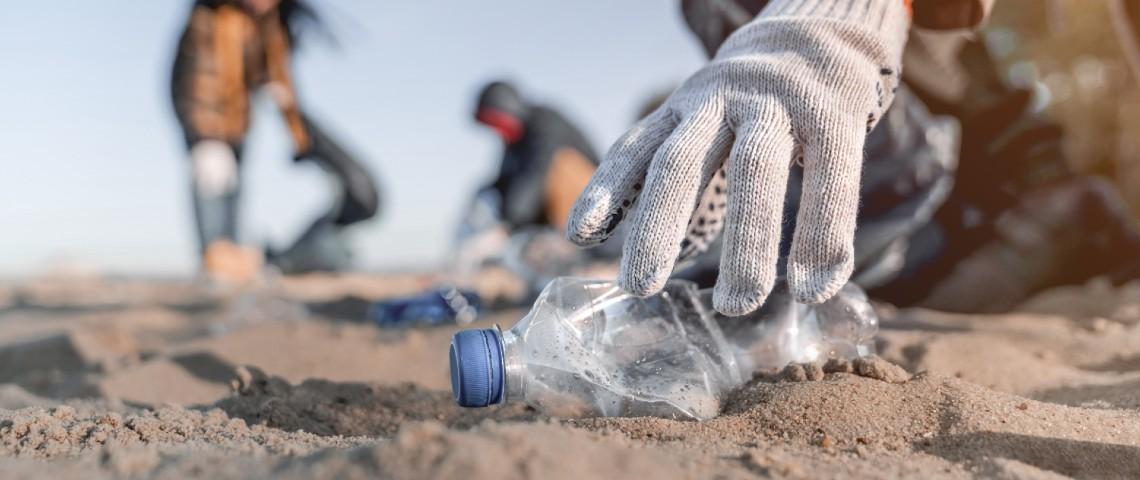 Personne en train de ramasser une bouteille en plastique sur la plage