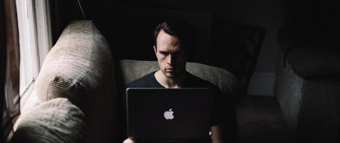 Un homme seul devant un ordinateur dans la pénombre