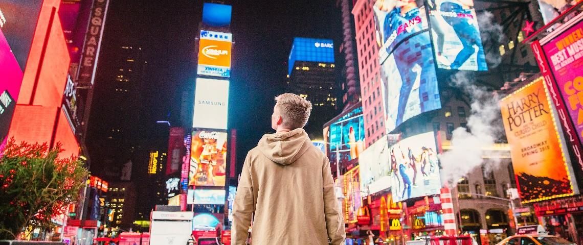 Adolescent de dos à Time Square, devant les affichages publicitaires lumineux