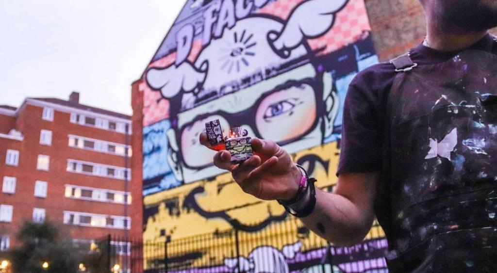 Le street artist D*face tenant le briquet Zippo qui reprend sa fresque murale
