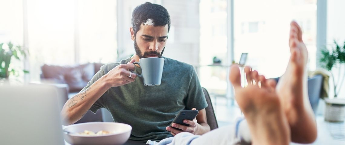 Homme tient une tasse et regarde son téléphone