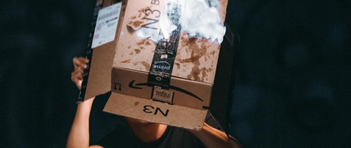 Un homme tient un carton Amazon en train de brûler