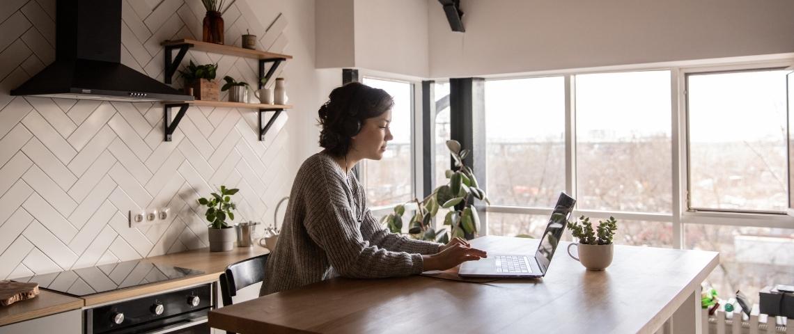 Une femme en train de télétravailler dans son appartement