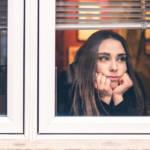 Une jeune femme regardant par la fenêtre