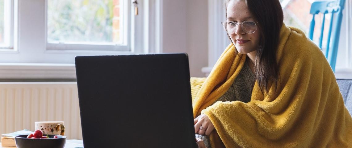 Une jeune femme, un plaid enroulé autour de ses épaules, sur son ordinateur
