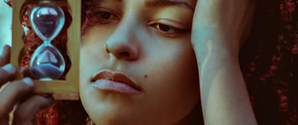 Une jeune femme s'ennuyant, tenant un sablier