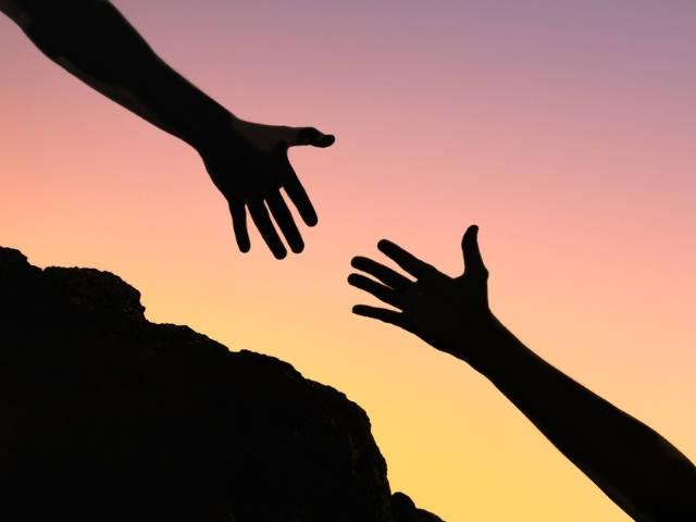 Une personne en train d'aider une autre personne à gravir un rocher