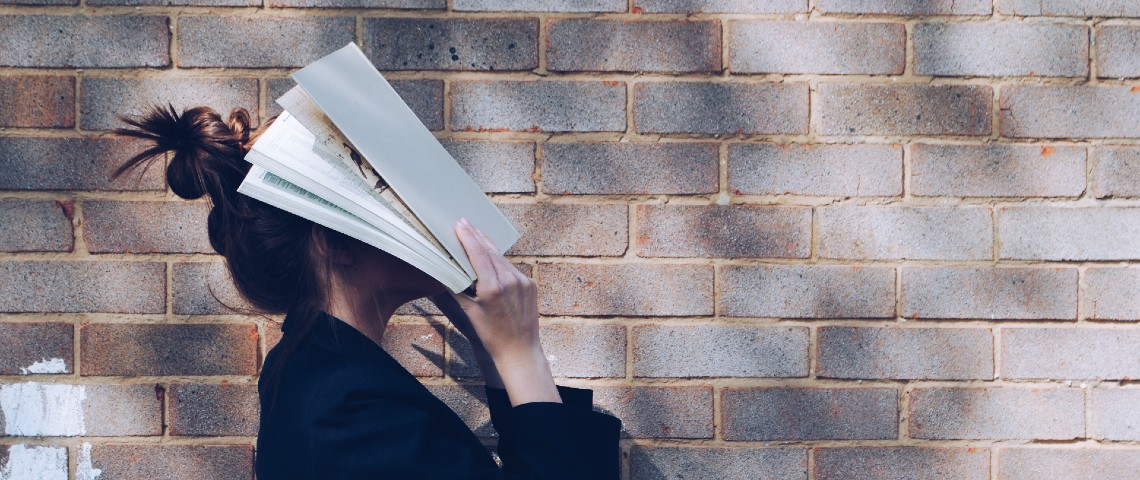 Une femme se cache le visage avec un livre