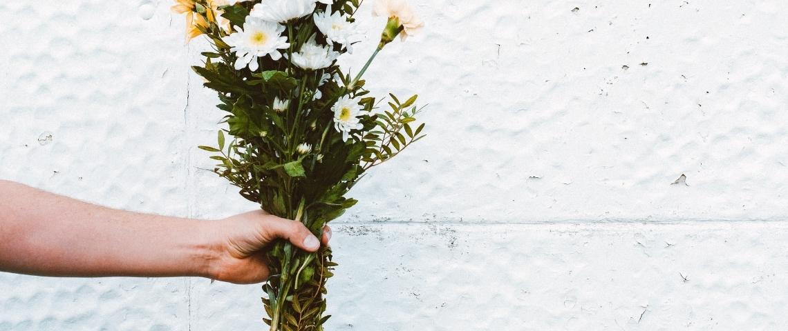 Une main tenant un bouquet de fleurs blanches