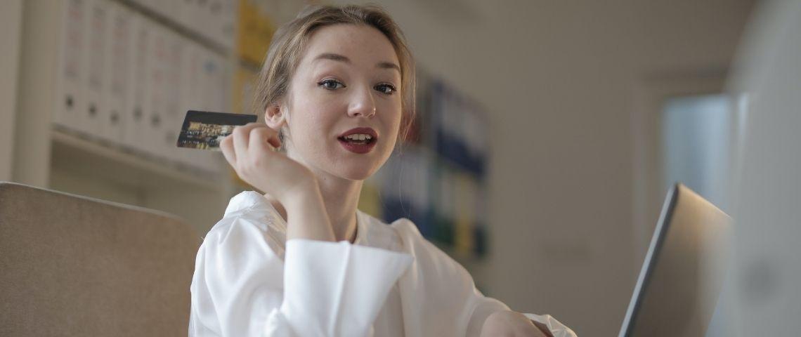 Jeune femme avec une carte bleue à la main