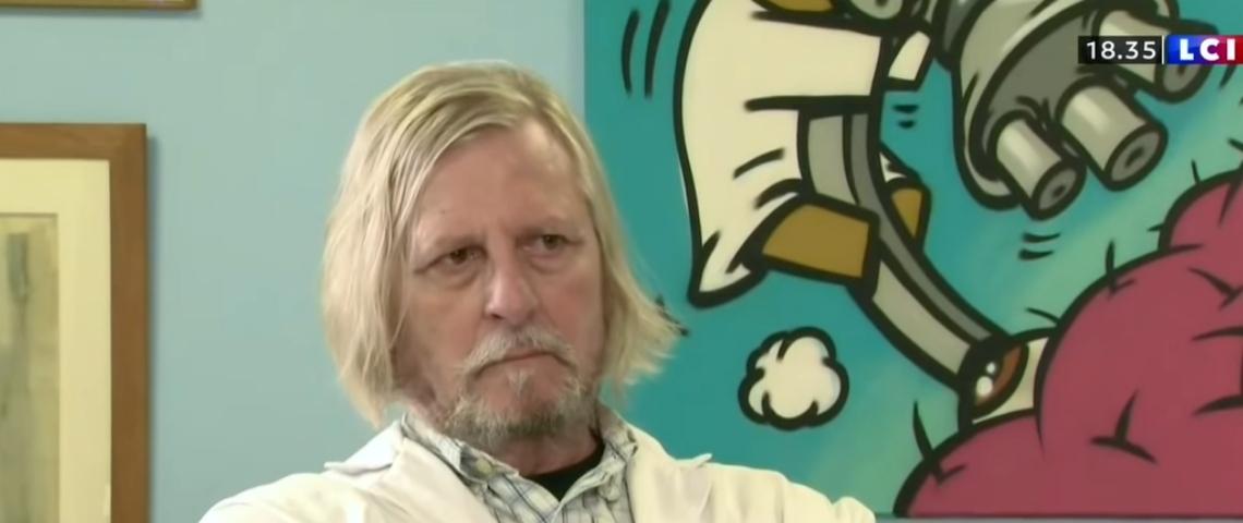 un homme avec une barbe et des cheveux blancs dans son bureau