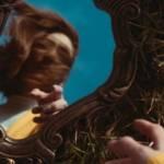 Une femme qui se regarde dans un miroir posé par terre