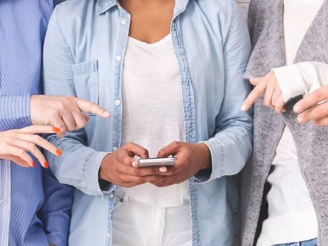 Des personnes en train de pointer le smartphone d'une personne au centre d'un groupe