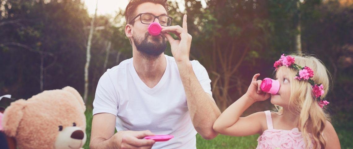 Un homme qui le thé avec une petite fille habillée en rose