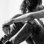 Homme torse nu, assis, la tête entre ses bras