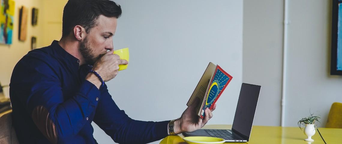 Un homme lit un livre devant son ordinateur portable