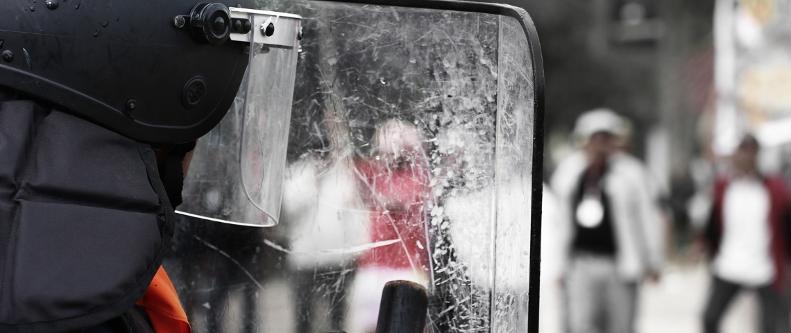 derrière le bouclier transparent d'un policier.