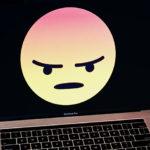 Un ordinateur portable affichant un smiley colérique