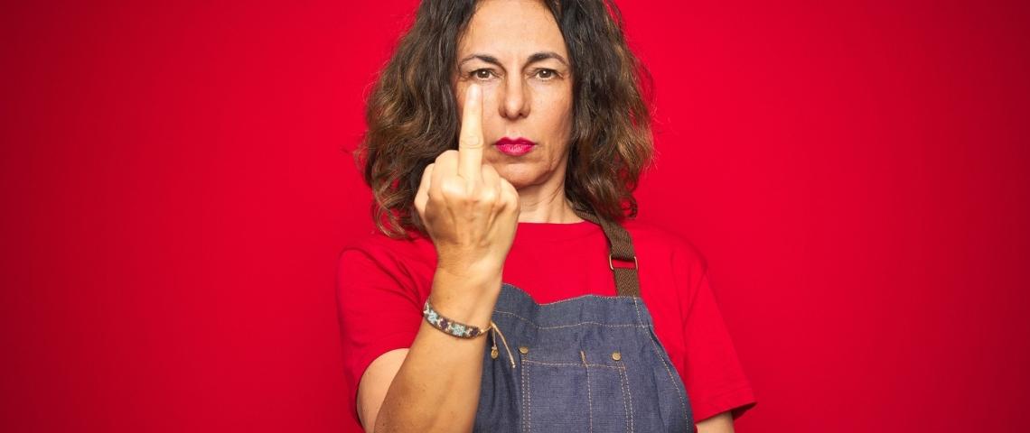 Une femme cheffe cuisinière en train de faire un doigt d'honneur