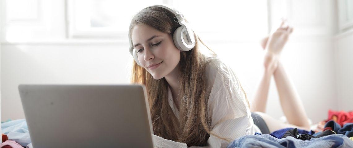 Jeune fille allongée sur son lit, devant un ordinateur avec un casque sur les oreilles