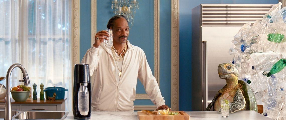 Snoop Dogg, un verre de sodastream à la main avec une tortue et des déchets de bouteilles plastiques derrière elle