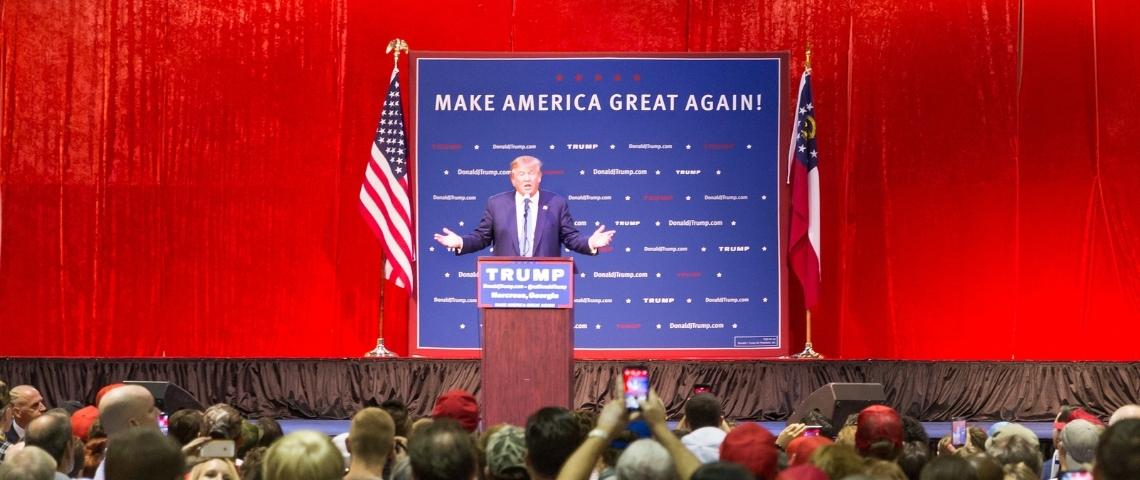 un meeting de Trump avec un fond rouge