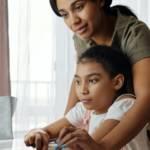 Une mère qui aide sa fille à faire ses devoirs devant l'ordinateur