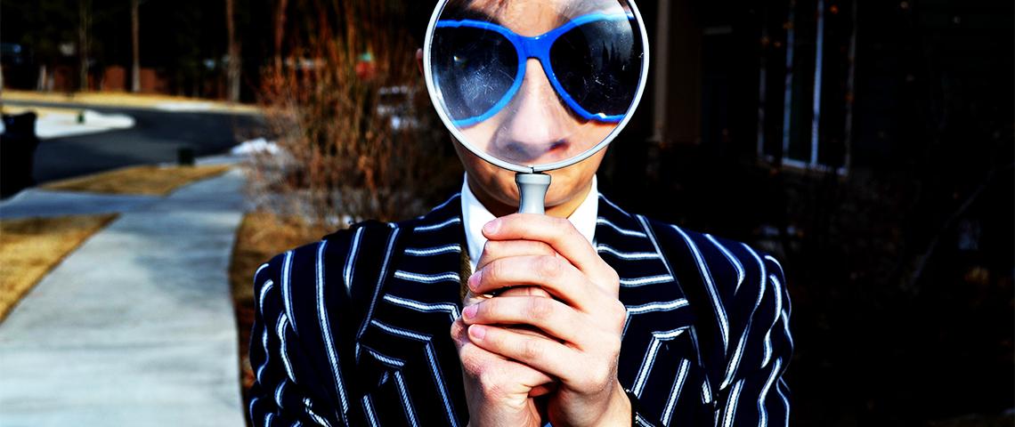 Un homme tenant une loupe devant ses yeux