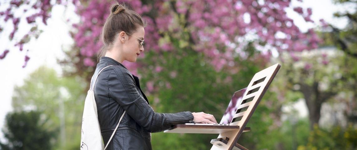 Dehors dans un parc, une jeune femme travaille sur son ordinateur