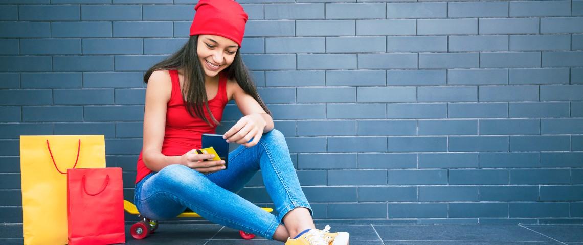 Adolescente assise par terre regarde son smartphone, avec une carte bancaire dans une main et des sacs de shopping à côté d'elle