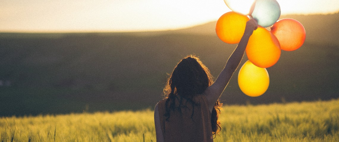 Une femme tient 5 ballons dans la nature