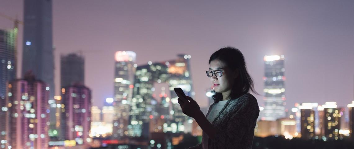 Une jeune femme regarde son smartphone dans un centre ville chinois entourée de building