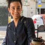Personne transgenre souriante prenant un café
