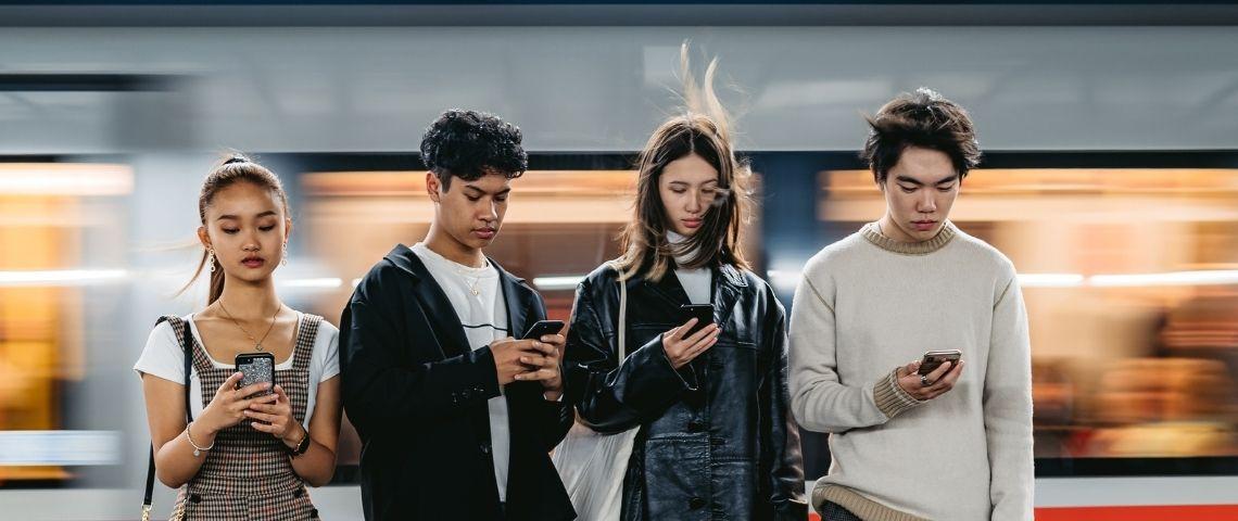 Quatre adolescents qui regardent leur téléphone portable