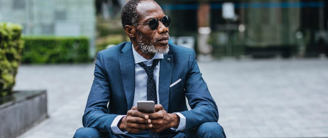 Un homme d'affaire noir consulte son smartphone
