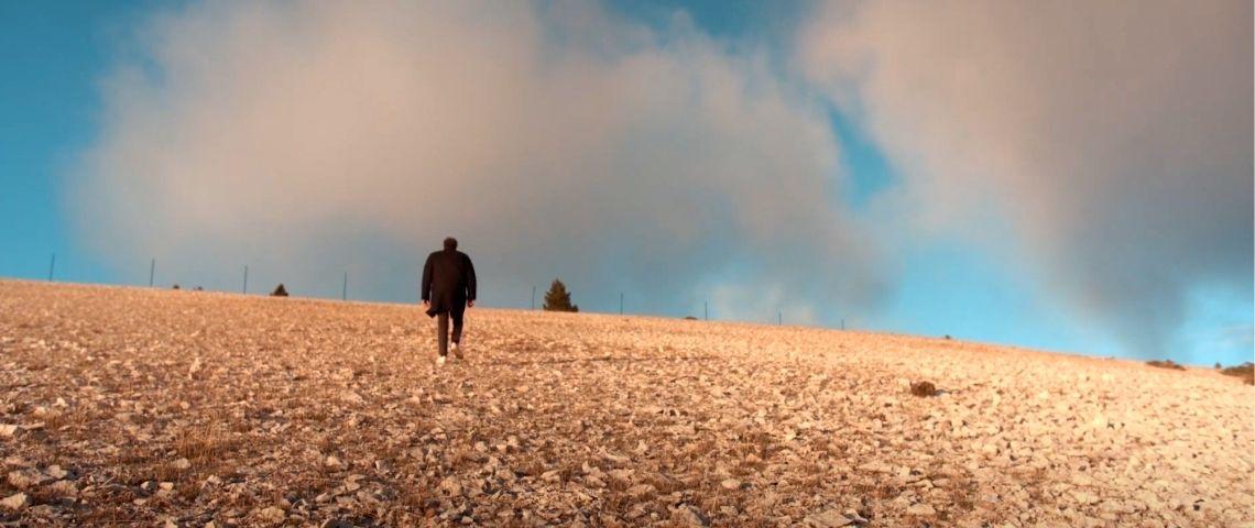 un homme marche vers l'horizon dans la nature