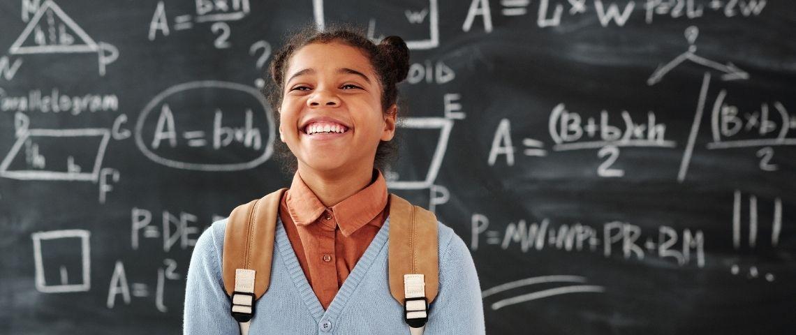 Jeune fille souriante devant un tableau d'école